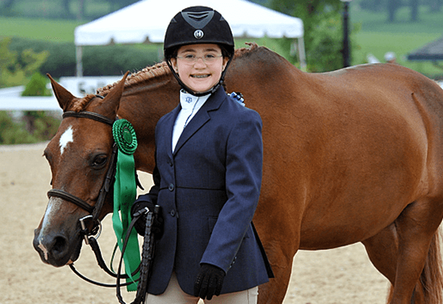 Alex Hershfield stands by her horse