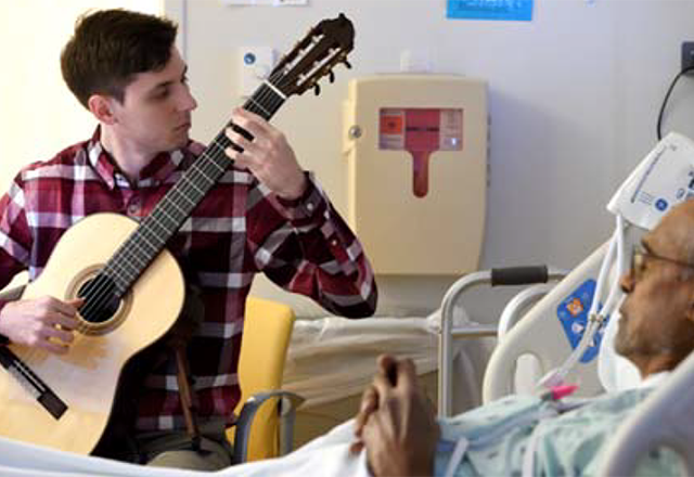 Jacob Lyerly plays guitar for a patient.