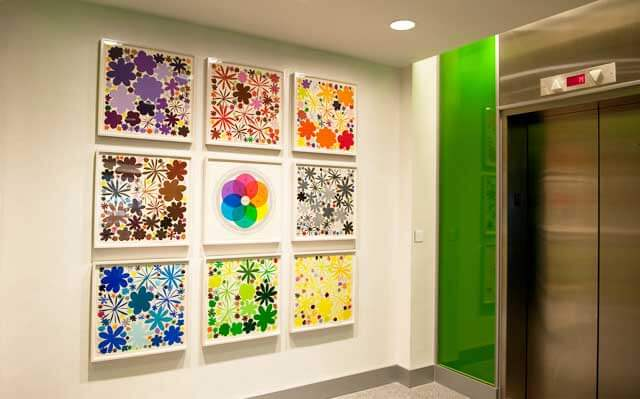 Nine pieces of artwork hung in a square pattern outside an elevator