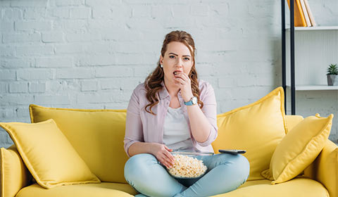 Woman eating a bowl of popcorn.