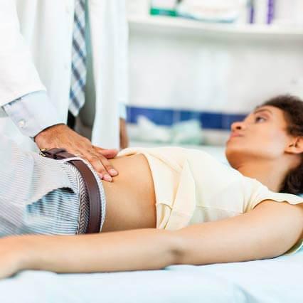 Doctor examines a patient's abdomen