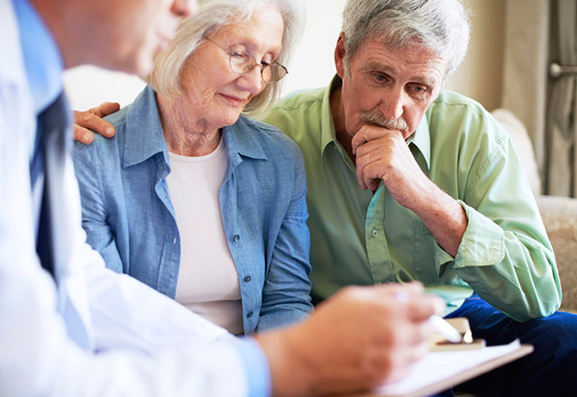 Older couple speak with a doctor in his office.