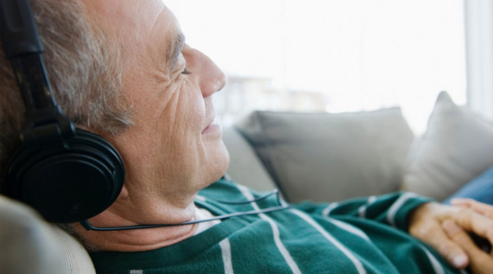 Older man listening to headphones