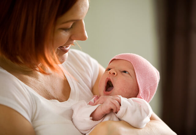 Mother holding yawning newborn baby