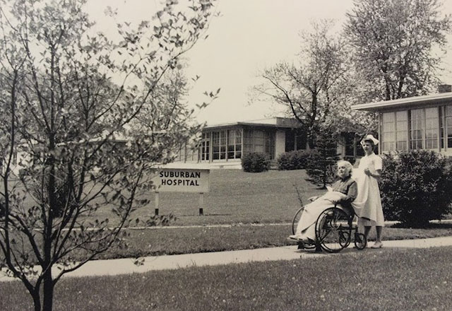 A nurse pushing a patient outside of the original Suburban Hospital