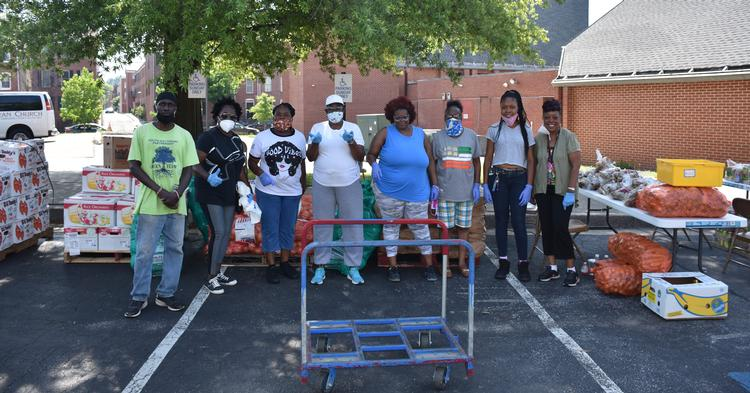 South Baltimore Partnership volunteers prepare to distribute fresh meat and produce to neighbors during the COVID-19 pandemic using a Baltimore Community ToolBank cart.