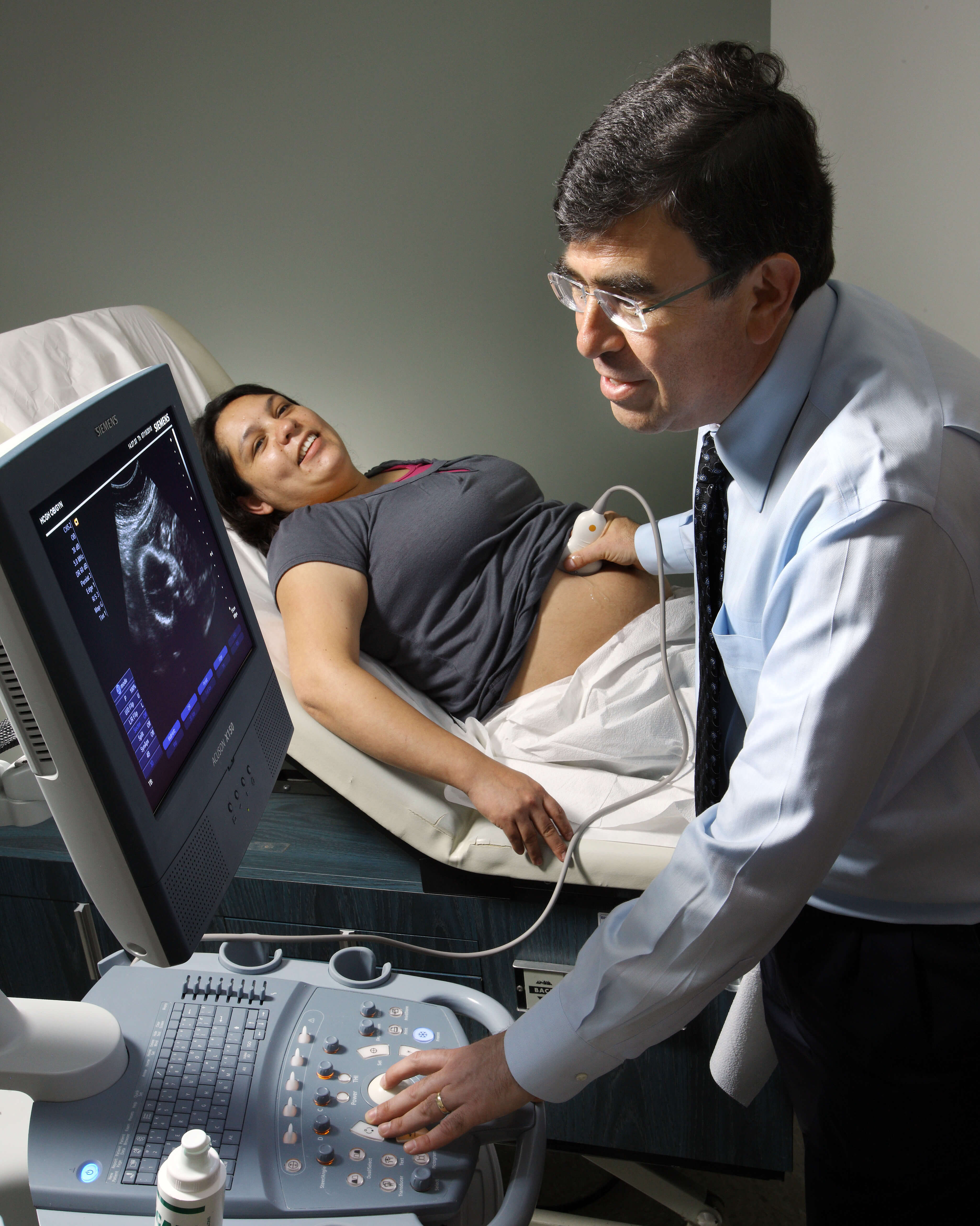 Dr. Kokkinakos performing an obstetric ultrasound on a new mom in an exam room with her parner looking on in the background