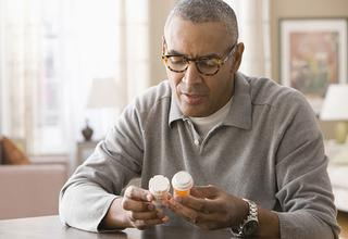 Senior male carefully reading two prescription bottles