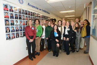 Certified nurses from Suburban Hospital's Professional Development Council help unveil the new Certified Nursing wall exhibit.
