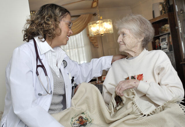 Female physician visiting an elderly female patient in her home