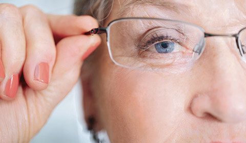 Woman adjusts her glasses