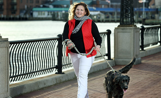 Mary walking her dog on a bridge in Annapolis