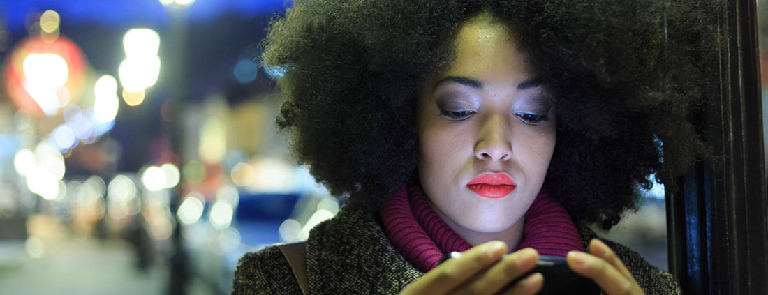 Woman checking her phone on a cold winter night.