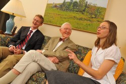 Bill Fritz '49, center, swaps war stories about his Hopkins Medicine experience with grandchildren Eben Clattenburg '14 and Lia Clattenburg Tron '07.