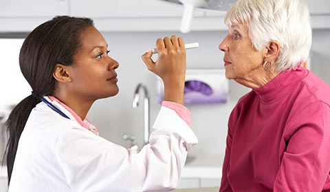 Eye doctor checks a senior patient's vision with a light.