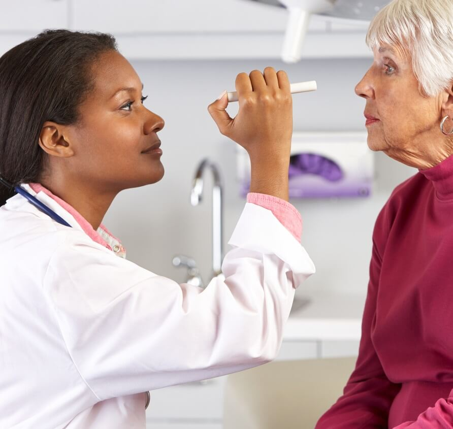 Eye doctor checks her patient's vision.