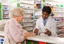 An elderly woman picking up her prescription from a pharmacist