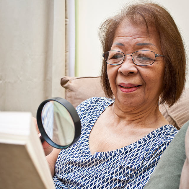 Woman using a magnifying glass as she reads.