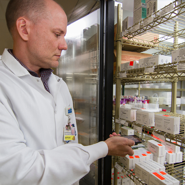 Photos shows immunology lab supervisor Matthew Morrow checking inventory using the JumpStock app.