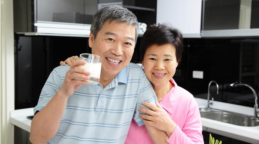man smiling holding a milk cup with wife by his side