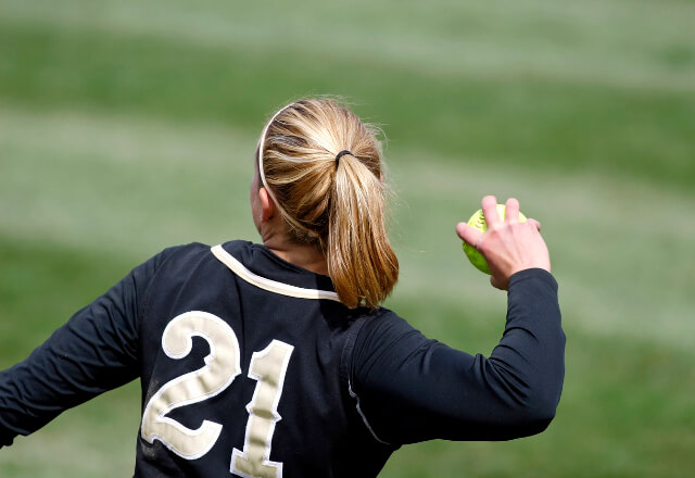 A softball player throwing a ball
