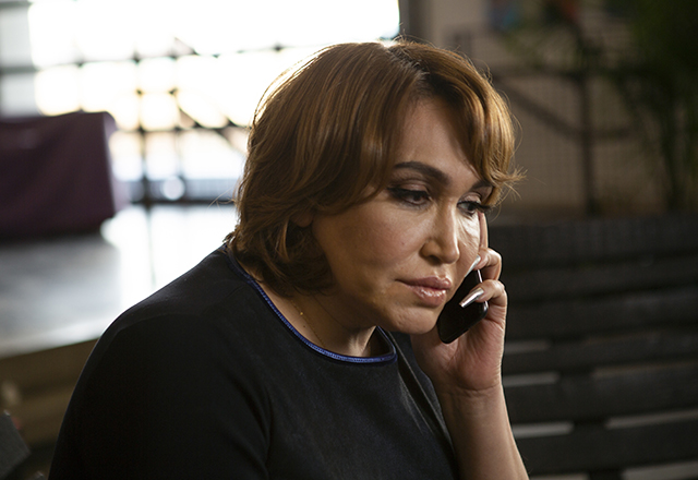 A transgender woman listens intently while on the phone.