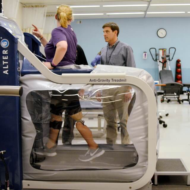 A woman with a leg prosthetic walking on an anti-gravity treadmill