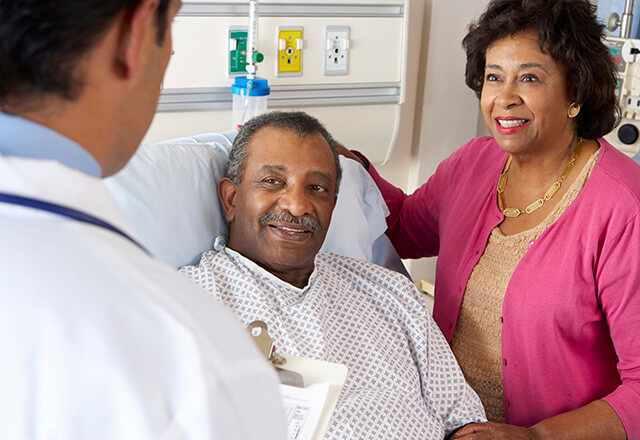 doctor talking to a patient in a hospital bed and his wife