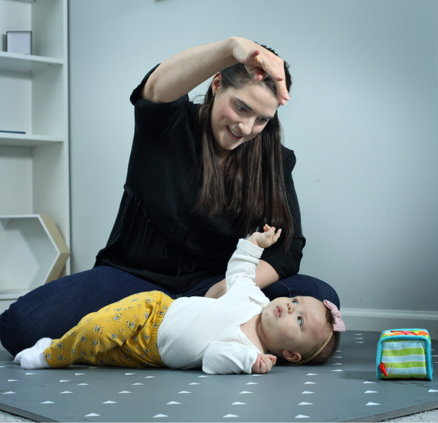 physical therapist encouraging baby Sofia to turn over