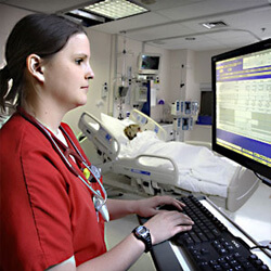 nurse typing on computer keyboard looking at computer monitor