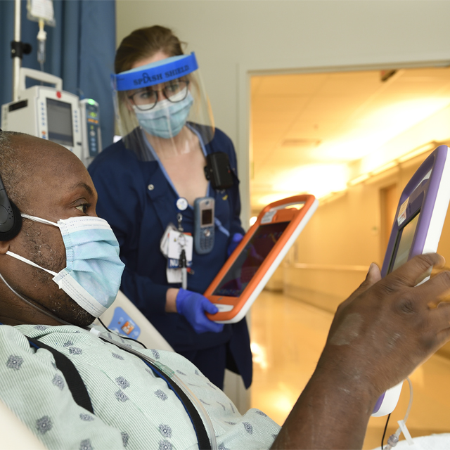 A photo shows a patient in the hospital using a tablet.