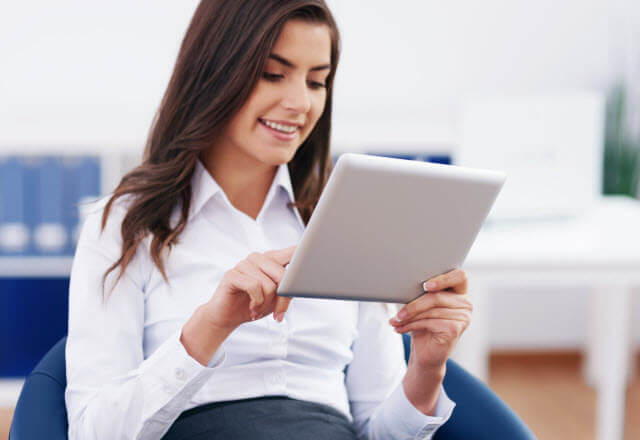 Seated woman browsing news site with a tablet.