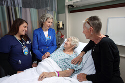 Toby Levin, center, talks to a Suburban Hospital patient about to be transferred to the Hebrew Home in Rockville, Md., about her father's positive experience at the home as the patient's daughter looks on. At left is oncology nurse Jennifer Simon.