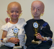 Two children with progeria smiling and holding trophies for finishing a research trial