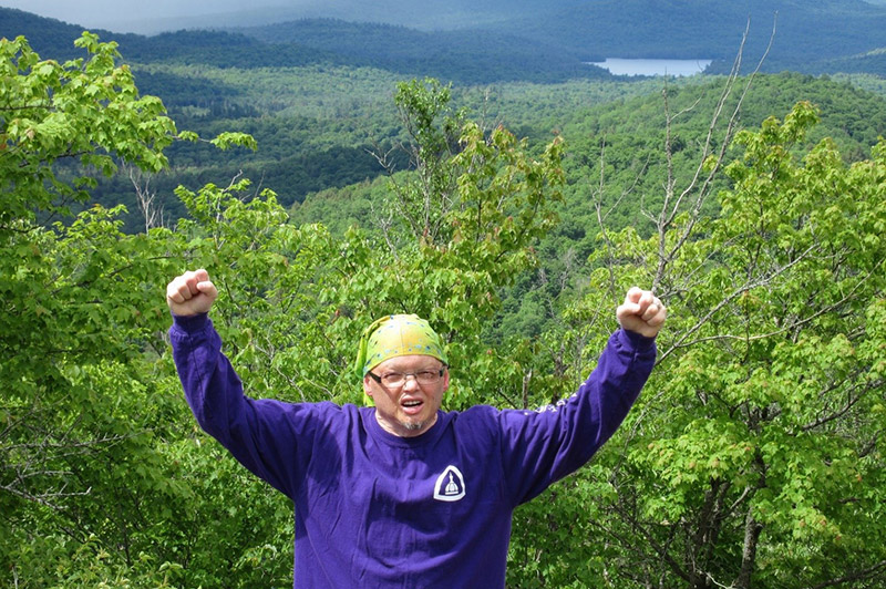 Craig throwing his hands up in celebration at the top of a hiking trail.
