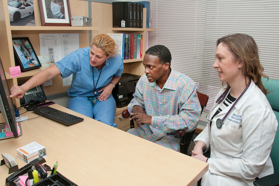 Two nurses showing a young man something on a computer