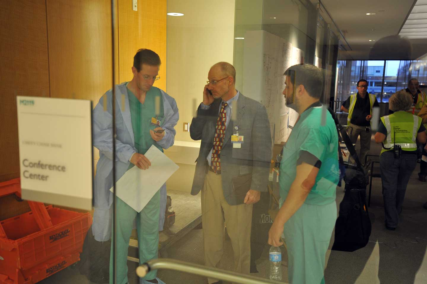 Clinicians take a moment to confer in the command center doorway.