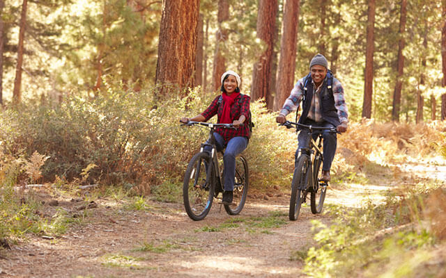Couple biking through a wooded trail.