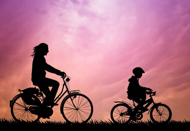 woman and a child riding bikes at sunset