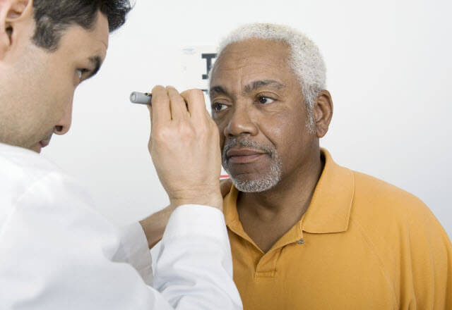 Eye doctor examining man's eyes