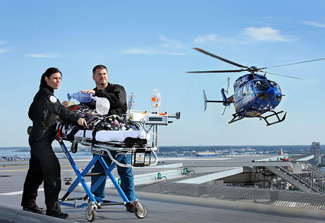 pediatric transport helicopter landing while staff push gurney on helipad