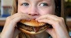girl biting a cheeseburger