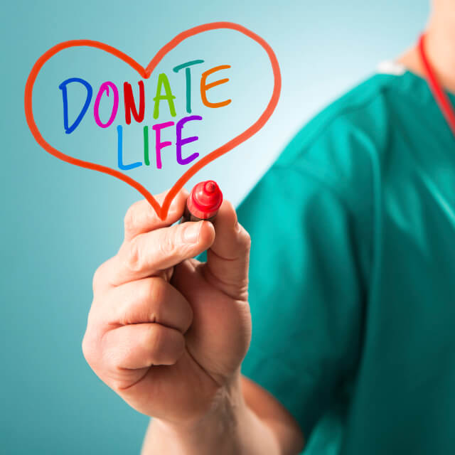 "A nurse writing ""Donate Life"" with a marker"