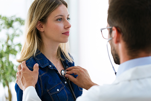 doctor using stethoscope on woman