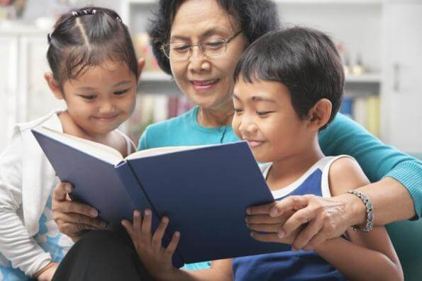 Grandmother reading with her two grandchildren.