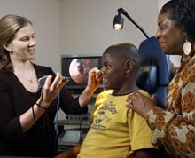 Dr. Margaret Skinner, pediatric ENT at Johns Hopkins, performs a nasal endoscopy on a patient while his mother watches.