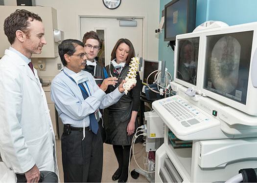 Pain Division Director Srinivasa Raja, MD examines a model of the spine with members of his team
