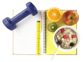 a handweight and breakfast food placed on a notebook