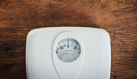 Weight scale on hardwood floor.