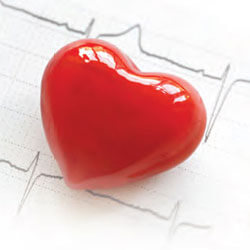 Shiny red plastic heart sitting on EKG results